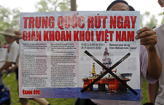 A protester holds a banner which reads 'Remove oil rig from Vietnam, China' during a rally against China in Hanoi