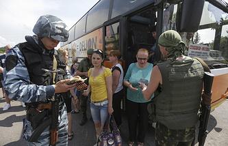 Ukrainian soldiers check a bus on a road near Sloviansk