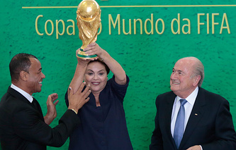Brazilian President Dilma Rousseff (C), holds the trophy of the FIFA World Cup 2014  next to FIFA's President, Swiss Joseph Blatter (R), and former Brazilian soccer player Cafu (L)