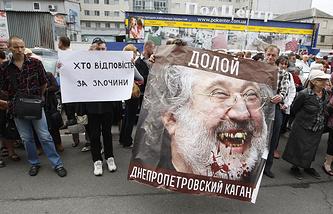 Demonstrators in Kiev hold a plackard featuring governor of the Dnepropetrovsk region Igor Kolomoisky