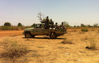 Nigeria soldiers drive past gymnasium in Chibok village from which the girls were kidnapped in mid-April