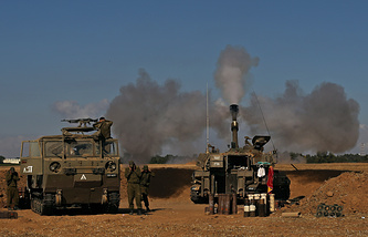An Israeli self-propelled 155mm howitzer fires towards the Gaza Strip