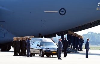 Bodies of victims in the Malaysia Airlines flight MH-17 crash are transferred to funeral hearses by Dutch military personnel during a ceremony at Eindhoven Airbase