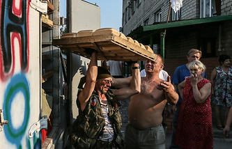 Member of the Donetsk People's Republic militia carries trays with bread for locals in Ilovaysk, Donetsk Region