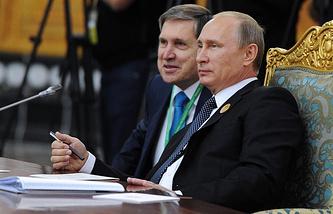 Russian President Vladimir Putin (R) and presidential aide Yuri Ushakov (L)