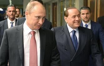 Russian President Vladimir Putin and former Italian Premier Silvio Berlusconi