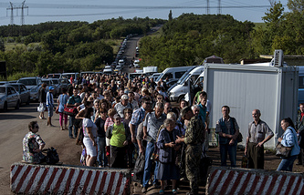 Residents of the Donetsk and Luhansk regions wait to cross a Ukrainian government forces' checkpoint