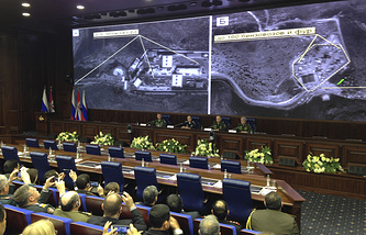 Russian top military officials speaking to the media in front of an aerial images of oil trucks near Turkey's border with Syria