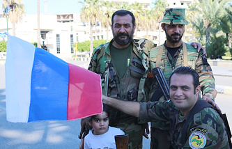 Syrian soldiers witgh a Russian flag in Tartus (archive)