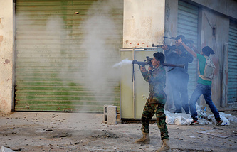 Libyan military soldiers fire their weapons during clashes with Islamic militias in Benghazi