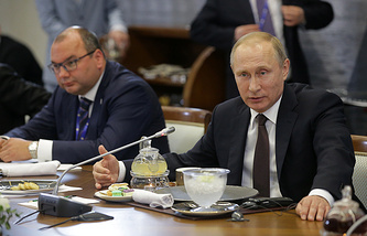 TASS Russian News Agency Director General Sergei Mikhailov (L) and Russia's President Vladimir Putin