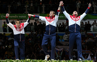 Gold medalists, Russia's Artur Akhmatkhuzin, Timur Safin and Alexey Cheremisinov (L-R) at an award ceremony for the Men's Team Foil Fencing event at the 2016 Summer Olympic Games in Rio de Janeiro