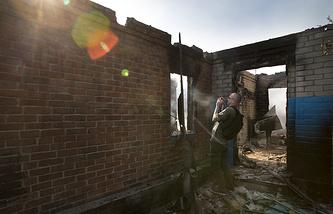 Journalist filming a destroyed house in Semyonovka village, Ukraine