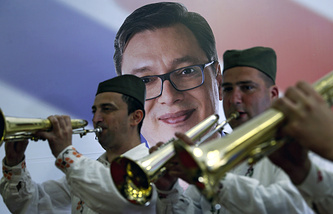 A trumpet band wearing traditional Serbian hats play in front of a picture of Serbian President-elect Aleksandar Vucic
