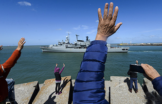 People wave to the Argentine destroyer as it leaves a Navy base in Mar del Plata to participate in the search of the missing submarine