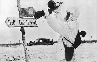 Советский солдат сбивает прикладом автомата немецкий дорожный указатель. 1944 г.