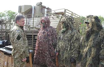 Президент Украины Петр Порошенко (слева) во время встречи с бойцами Национальной гвардии на территории штаба антитеррористического центра