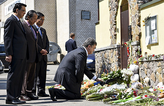 Президент Украины Петр Порошенко (справа) во время возложения цветов у посольства Малайзии в память о погибших пассажирах