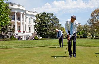 Президент США Барак Обама и вице-президент Джо Байден играют в гольф на лужайке Белого дома