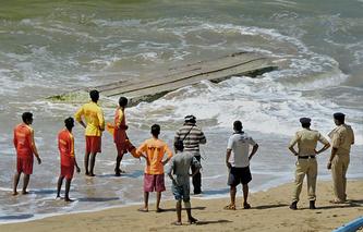 Спасатели и полицейские стоят возле лодки, на которой перевернулись российские туристки. Пляж в Панаджи (южное побережье Гоа). 28 октября 2014 года
