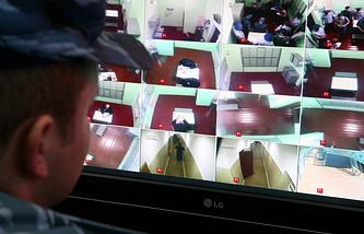 Охранник у экрана системы видеонаблюдения на территории колонии