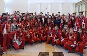 Владимир Путин во время фотографирования с призерами зимней Универсиады-2015