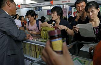 Жители Пхеньяна смотрят на стенд с лекарствами на выставке