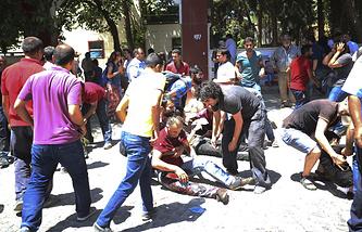 Люди помогают раненым после взрыва на юго-востоке Турции в городе Суруч