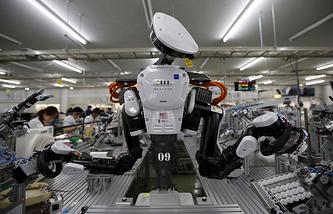 Человекоподобный робот работает на сборочной линии на заводе компании Glory Ltd., производителя автоматических распределительных устройств
