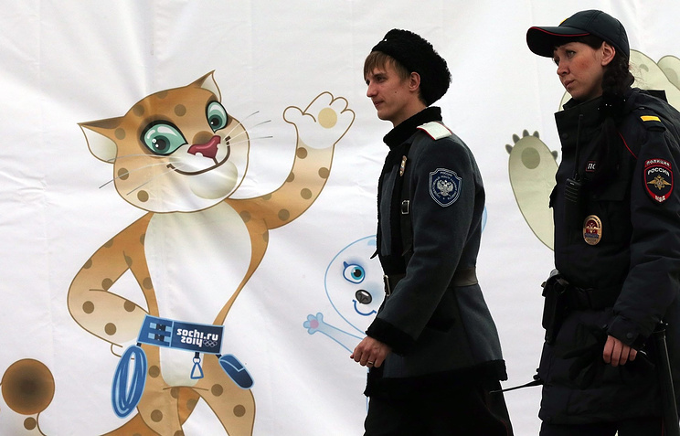 A Russian cossack and a police officer walking past a poster featuring one of the symbols of the Sochi Olympics