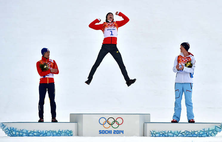 Gold medalist Eric Frenzel (C) of Germany, flanked by silver medalist Akito Watabe (L) of Japan and bronze medalist Magnus Krog of Norway, celebrates during the flower ceremony after Nordic the Combin
