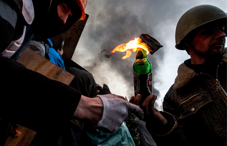 A protester preparing to throw a Molotov Cocktail
