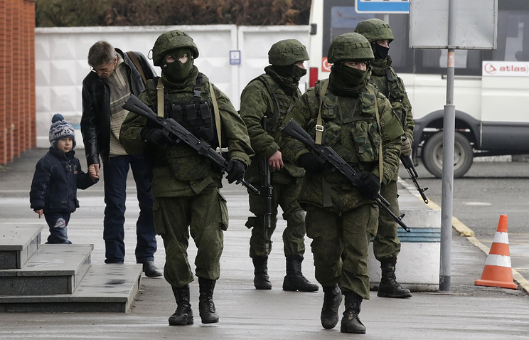 Unidentified armed men in military uniform patrol near a building at the airport in Simferopol, Crimea