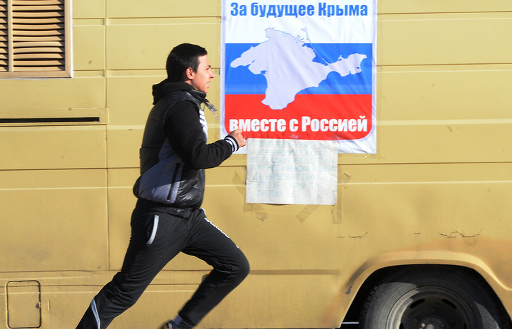 A poster with Russian national flag colours and Crimea's coastline configuration calling to vote for Crimea's future at referendum in Simferopol