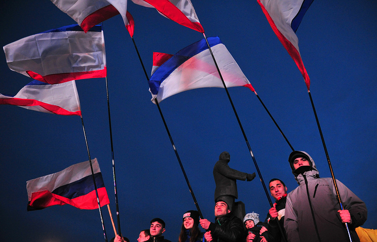Demonstrators holding Crimean and Russian flags in Simferopol