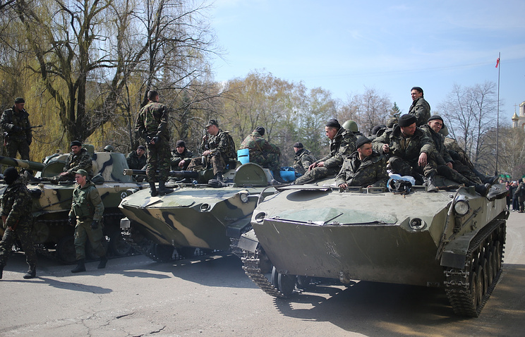 Donbass militia on captured armoured military vehicles in the town of Sloviansk on Apr. 16