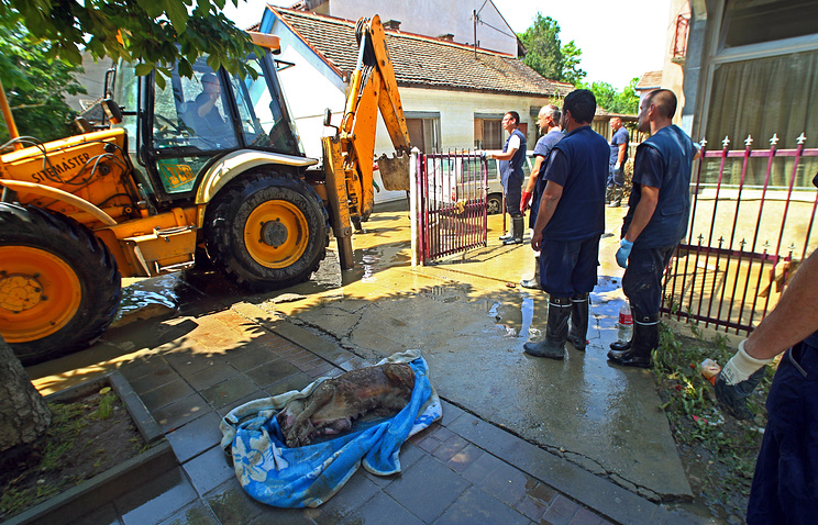 People clean the city destroyed by floods in Obrenovac, Serbia