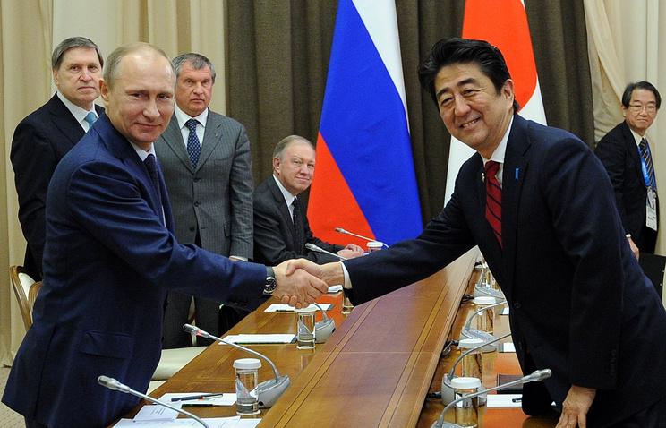 Russian President Vladimir Putin (L) and Japanes Prime Minister Shinzo Abe
