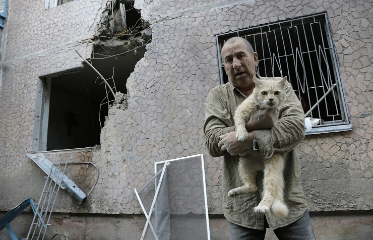 A man carries his injured cat in front of his damaged house after shelling in the city of Sloviansk