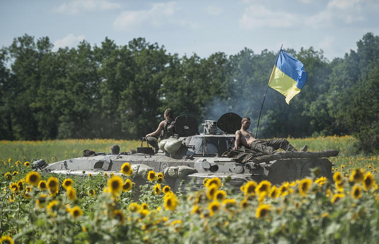 Ukrainian troops ride on an APC