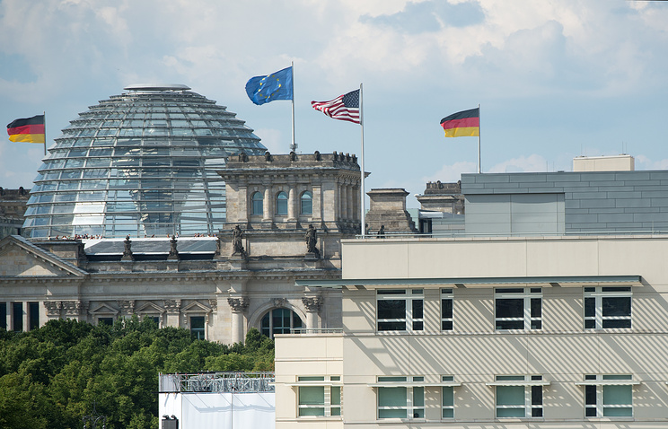 US embassy with the US flag in Berlin and the German Reichstag building in the background