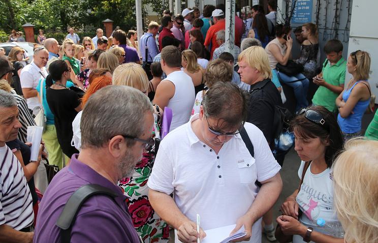 People gathering near the office of Labirint travel agency