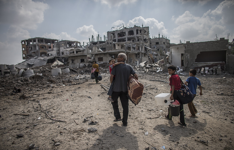 A Palestinian man and his sons return to their home in the Gaza Strip