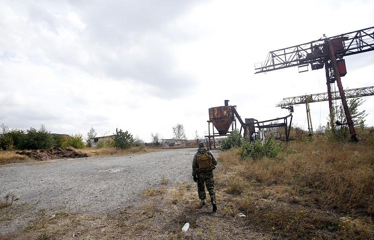 A militia fighter guards a mass grave found in eastern Ukraine