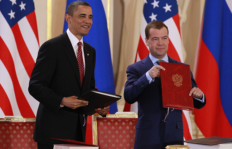 Barack Obama holds the signed New START treaty with Dmitry Medvedev in Prague, April 8, 2010
