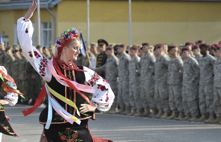 Ukrainian woman in national dress dances during the opening ceremony of joint military exercises near the city of Lviv, Ukraine