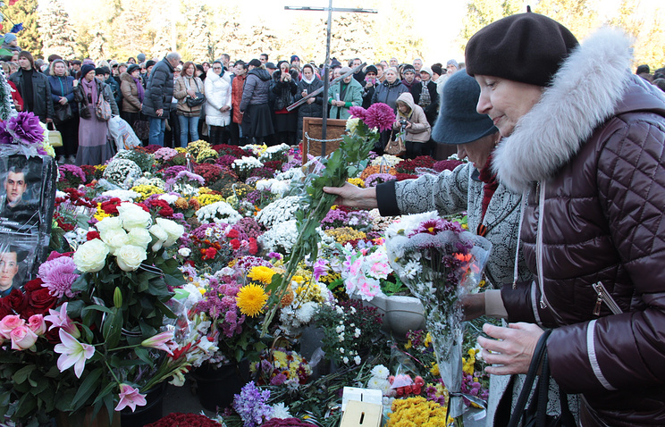 People lay flowers during a rally to remember federalization supporters who died on 2 May 2014 in Odessa