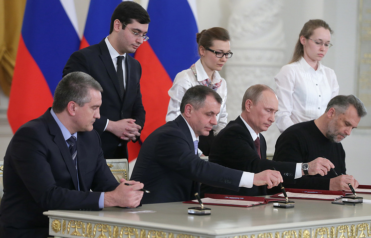 Crimea's head Sergey Aksenov, Crimean Supreme Council chairman Vladimir Konstantinov, Russian president Vladimir Putin, and Sevastopol head Alexey Chalyi signing a treaty on making the Republic of Crimea part of Russia