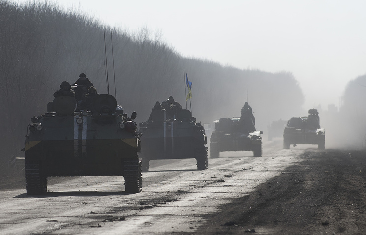 Ukrainian troops riding on an armored vehicles ahead of self-propelled artillery (archive)