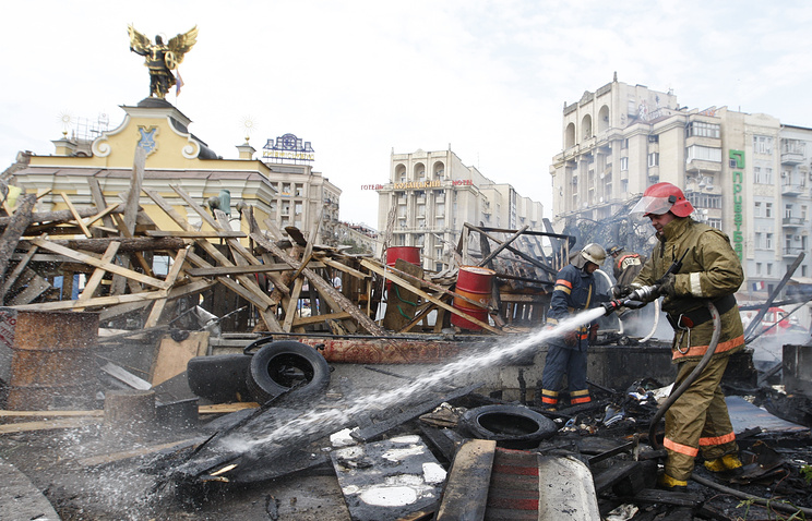 Fighter taking out flames at Maidan activists set tyres on fire to protest against clearing Kiev's Independence Square (archive)